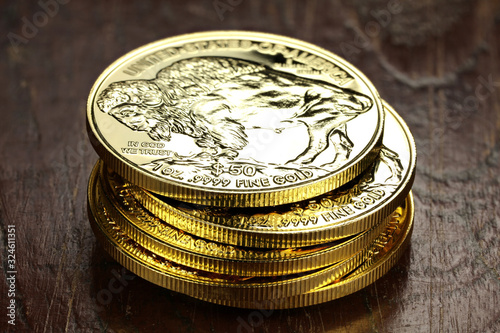 Photo 1 ounce American Buffalo gold bullion coins on wooden background