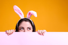 Cropped Studio Portrait Of Young Beautiful Woman Wearing Traditional Bunny Ears Headband For Easter Hiding Behind Pink Wall. Brunette Female With Wavy Hair Over Yellow Background. Close Up, Copy Space