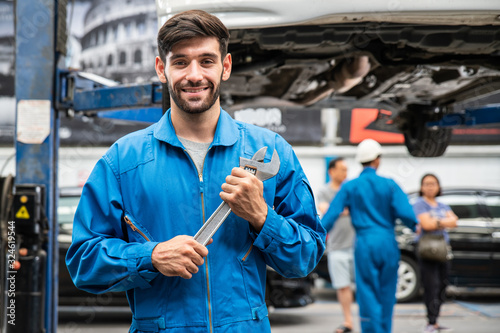 Fotomural Mechanic standing and hold a wrench with blur his assistant talking with customers in the background