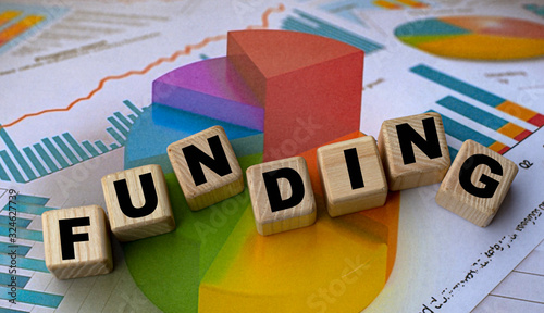 Fototapeta The concept of the word funding on cubes against the background of the graph obraz