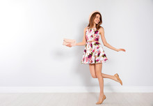 Young Woman Wearing Floral Print Dress With Clutch Near Light Wall. Space For Text