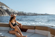canvas print picture - Relaxed woman in sun hat enjoying ocean voyage, sailing on the luxury yacht near the beautiful rocky coast during a sunset. Concept of a summer rest on the sea
