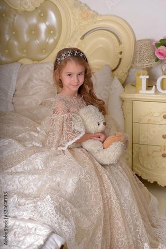vintage portrait of a little girl in alabaster elegant dress with a toy bear Wallpaper Mural