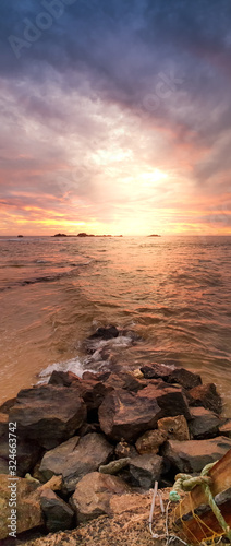 Fototapeta Beautiful panoramic photo of sunrise over the ocean and sharp cliffs on the beach obraz