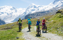 Happy Family Riding A Bike In A Beautiful Mountain Landscape During Vacation In The Swiss . Mountainbike Tour With View.