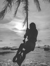 Black And White Silhouette Of Young Woman Swinging On The Swing On Palm At Ocean Beach