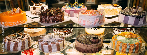 Fotografia Pastry shop glass display with selection of cream or fruit cake.