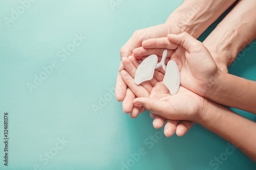 Obraz Adult and child hands holding lung, world tuberculosis tb day, world no tobacco day, lung cancer coronavirus, covid-19 virus, pandemic,  eco air pollution; organ donation concept - fototapety do salonu