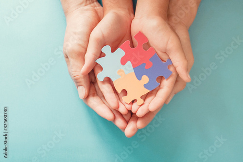 Photo Adult and chiild hands holding jigsaw puzzle shape, Autism awareness, Autism spe