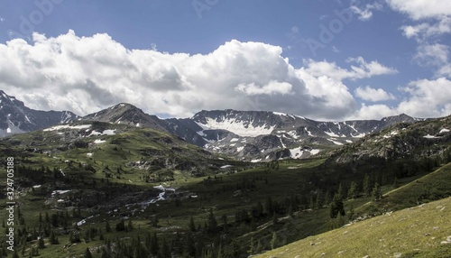 Wide shot of a mountain range with trees around and a thick layer of clouds in the sky