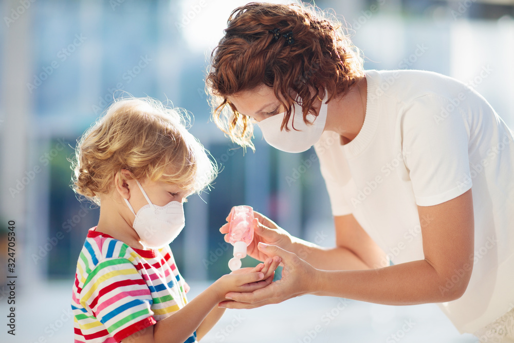 Fototapeta Mother and child with face mask and hand sanitizer