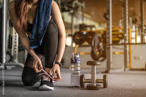 Fototapeta premium Kobiety za pomocą rąk zawiązują buty, mają hantle i butelkę wody. Przygotuj się do ćwiczeń na siłowni o zachodzie słońca. fitness, trening, ćwiczenia na siłowni, styl życia i pojęcie zdrowego.