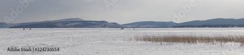 Panorama of a snowy stagnant large lake with mountains on the horizon Wallpaper Mural