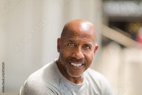 Happy mature African American man smiling outside.