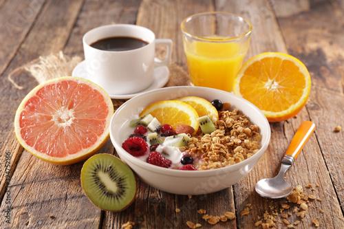 Fototapeta healthy breakfast with muesli and fruit, coffee cup and orange juice obraz