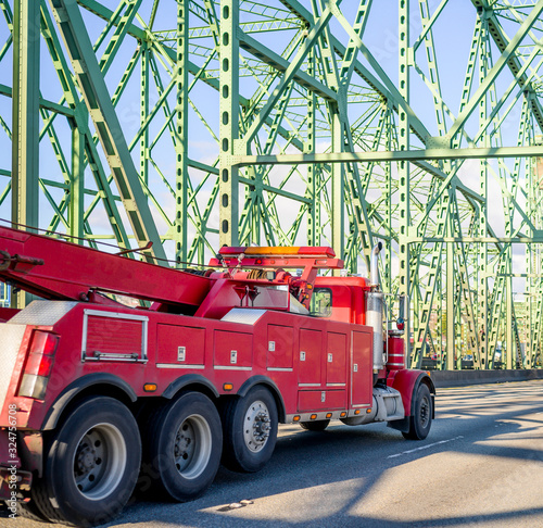Fototapeta Big rig powerful towing semi truck for tow large transportation driving on truss arched bridge obraz