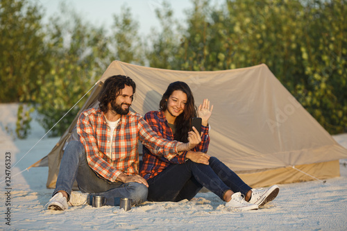 Fototapeta Happy Couple With a Smartphone in the Camp Near the Tent Outdoors obraz