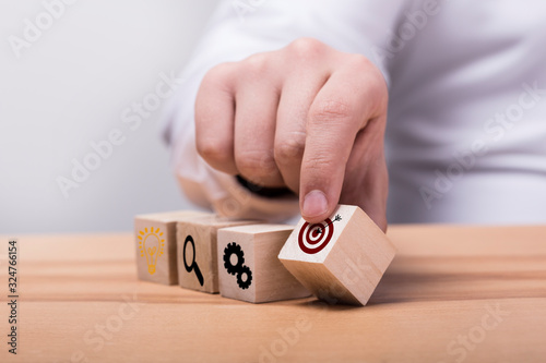Fototapety, obrazy: Concept of business strategy and action plan. Businessman hand putting wood cube block on top with icon