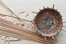 Top View Of The Process Of Weaving A Decorative Basket From Tubes Twisted From Tinted Newsprint On A Wooden Table. Hobbies And Handmade. Flat Lay, Close-up