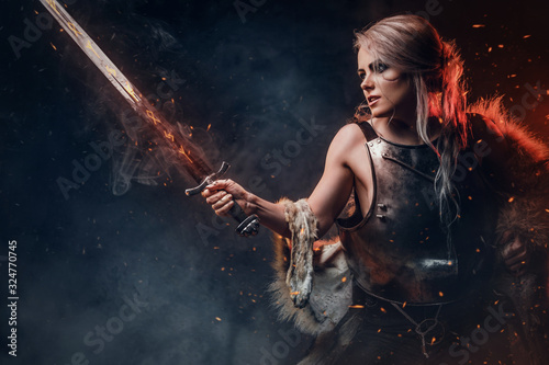 Portrait of a beautiful warrior woman holding a sword wearing steel cuirass and fur Canvas Print