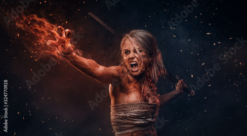 Photographie Fantasy woman warrior wearing rag cloth stained with blood and mud in the heat of battle