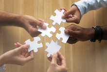 Hands Of Diverse Team Members Assembling Jigsaw Puzzle Close Up
