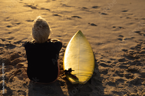 Old woman with a surfboard at the beach