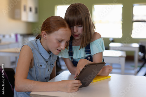 Schoolgirl looking at a tablet computer together in an elementary school classroom