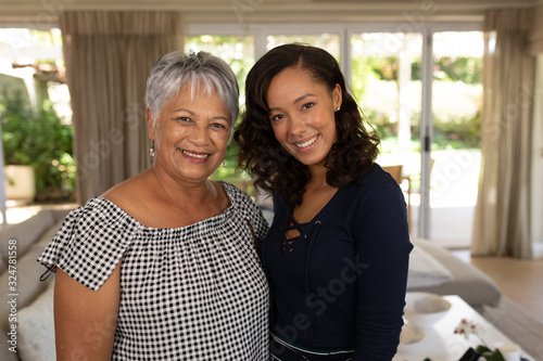 Two women smiling to camera at home