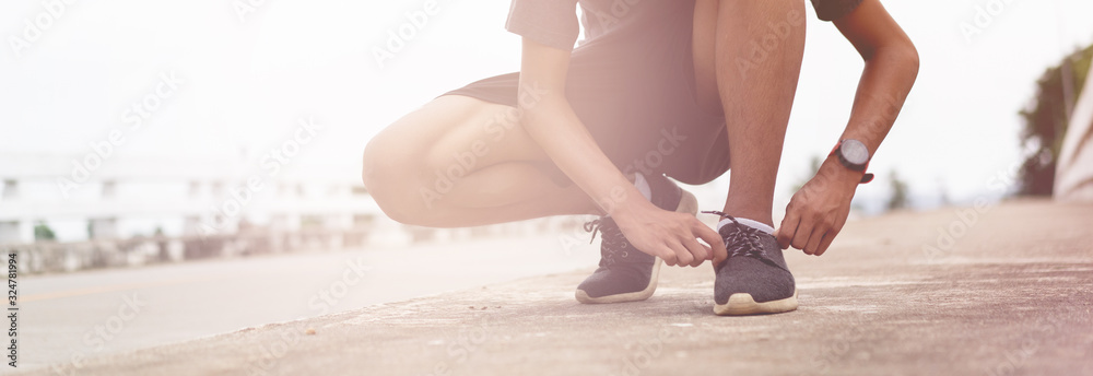 Fototapeta Tie a shoe,Asian male jogger athlete training and doing workout outdoors on a street, He tying laces for jogging on road with running shoes. Runner getting ready for exercise. Sport lifestyle concept