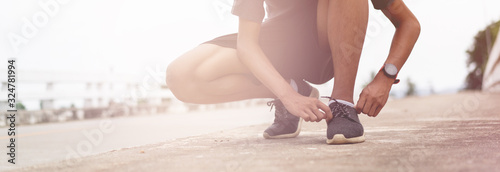 Fotomural Tie a shoe,Asian male jogger athlete training and doing workout outdoors on a street, He tying laces for jogging on road with running shoes