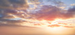 Dramatic sunset background of orange and yellow clouds against a blue sky background.