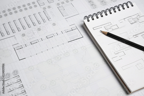 Notebook, pencil and building blueprint on worktable Canvas-taulu