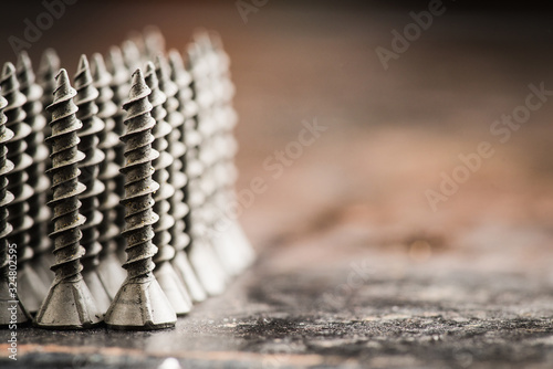 Obraz Tapping screw made of steel on the dark rustic background. Selective focus. Shallow depth of field. - fototapety do salonu