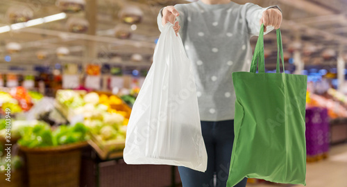 Photo consumerism and eco friendly concept - woman holding reusable canvas tote for fo