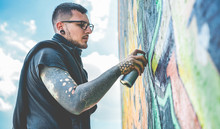 Tattooed Graffiti Writer Painting With Color Spray His Dark Picture On The Wall - Contemporary Artist At Work - Urban Lifestyle, Street Art Concept