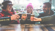 Group Of Happy Friends Drinking Beer Outdoor At Bar Restaurant - Friendship Concept With Young People Having Fun Together At Cool Vintage Pub - Soft Focus On Right Pint Glass
