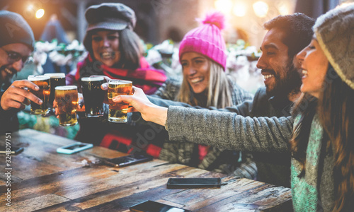 Fototapeta Group of happy friends drinking and toasting beer at brewery bar restaurant - Friendship concept with young people having fun together at cool vintage pub - Focus on right pint glass obraz