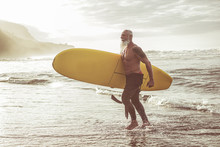 Senior Fit Guy Walking With Longboard After Surfing At Sunset - Mature Tattooed Man Having Fun Doing Extreme Sport On Tropical Beach - Joyful Elderly Lifestyle And Travel Concept - Focus On Male Body