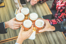 Group Of Friends Enjoying A Beer In Vintage Pub - Young People Hands Cheering At Bar Restaurant - Friendship, Party, Nightlife And Youth Concept - Focus On Bottom Hand Glass