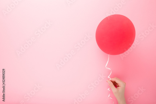 Платно Young woman hand holding one red balloon on light pink background