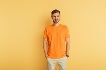 smiling young man in orange t-shirt standing with hands in pockets on yellow background