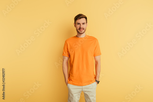 Fotografia smiling young man in orange t-shirt standing with hands in pockets on yellow bac