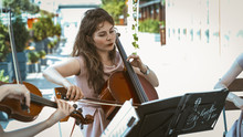Young Lady Playing Cello In String Orchestra