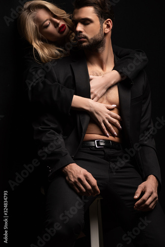 young woman embracing sexy man in suit sitting on chair isolated on black Fototapete