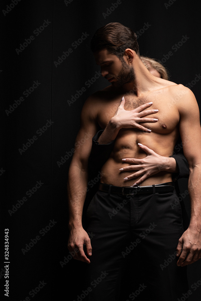 Fototapeta young woman touching sexy man isolated on black