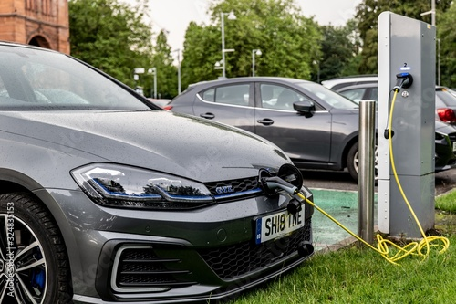 The Volkswagen Golf GTE electric plug-in car charged at the public charging station with green energy to get ecological mean of transportation