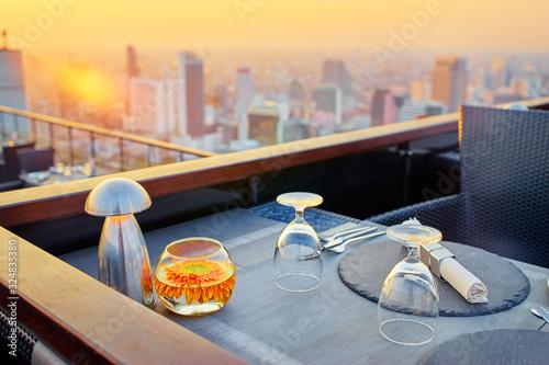 Valokuvatapetti Table setting on roof top restaurant with megapolis view, Bangkok Thailand