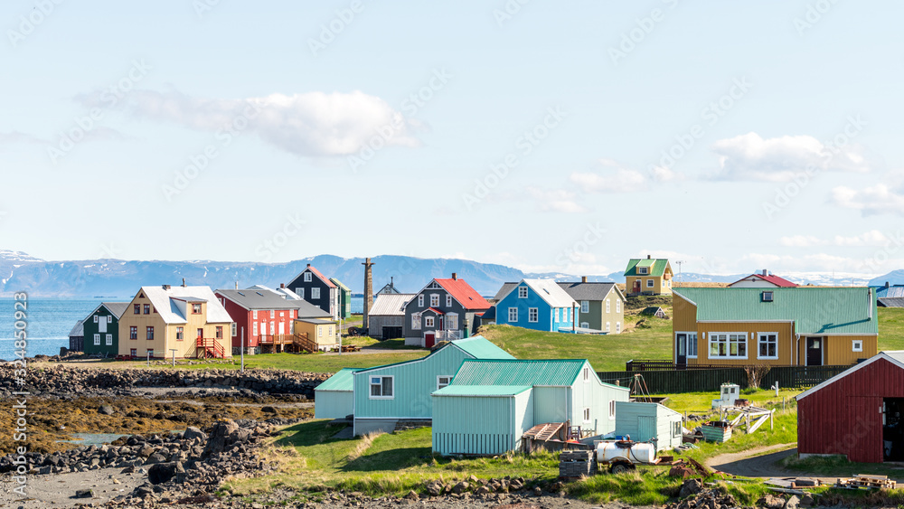 Fototapeta Colorful buildings and the charming city of Flatey Island in Iceland just outside Stykkisholmur and the Westfjords. Blue sky and sunny weather. Explore and traveling concept.