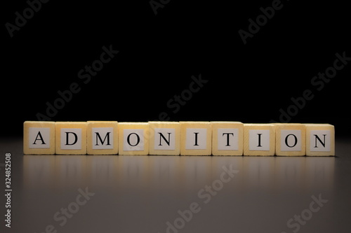 The word ADMONITION written on wooden cubes isolated on a black background Canvas Print